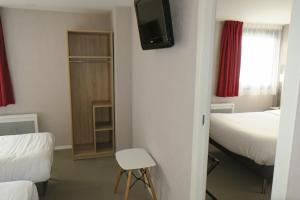 A bed or beds in a room at Brit Hotel La Ferte Bernard