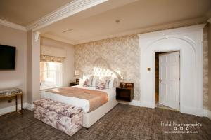 A bed or beds in a room at Makeney Hall Hotel