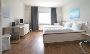 A bed or beds in a room at Pierspeicher Boutique Hotel