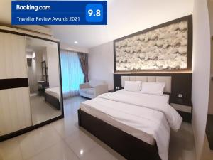 A bed or beds in a room at Apartemen Grand Kamala Lagoon Studio By Bonzela Property