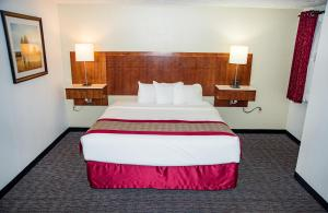 A bed or beds in a room at Ramada by Wyndham Cedar City