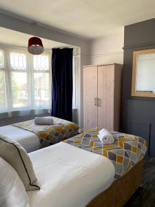 A bed or beds in a room at Exton House -Huku Kwetu 4 Bedroom House- Luton Airport - Group Accommodation - up to 7 people