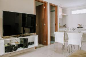A television and/or entertainment centre at Qavi - Apartamento aconchegante na Praia de Pirangi #VilaImperial