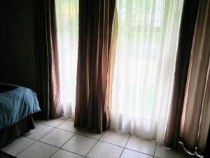Кровать или кровати в номере Rustenburg Guesthouse