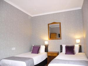A bed or beds in a room at West Park Hotel