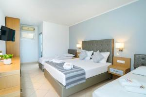 A bed or beds in a room at Sunny Hotel Thassos