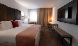 A bed or beds in a room at La Laguna Gran Hotel