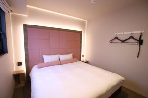 A bed or beds in a room at Doutonbori Crystal Hotel