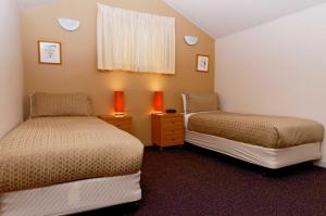 A bed or beds in a room at Squatters Run Apartments