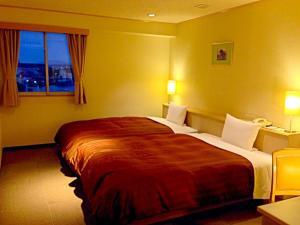 A bed or beds in a room at Kokura Bay Hotel Daiichi