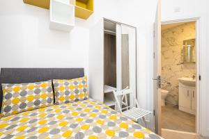 A bed or beds in a room at En Suite Rooms, TUFNELL PARK - SK