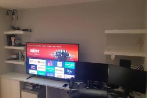 A television and/or entertainment center at Riverside Apartment - Serene