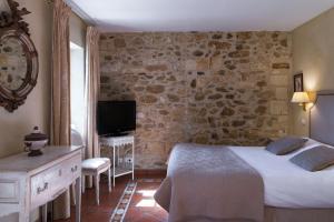 A bed or beds in a room at Najeti Hôtel la Magnaneraie