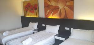 A bed or beds in a room at Heathrow Inn Hotel
