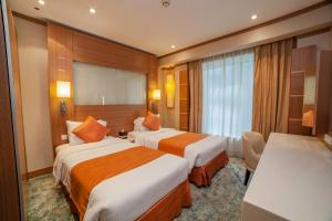 A bed or beds in a room at Grand Stay Hotel Dubai