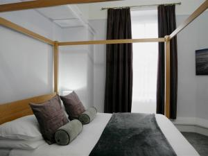 A bed or beds in a room at Norton House Hotel - Mumbles