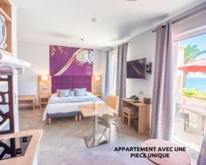 A bed or beds in a room at Hôtel et Appart Hôtel Les Flots Bleus