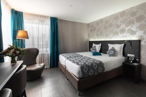 A bed or beds in a room at Mercure Bale Mulhouse Aeroport
