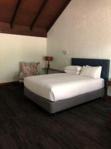 A bed or beds in a room at Olde Horsham Motor Inn
