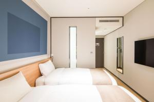 A bed or beds in a room at Ibis Ambassador Suwon