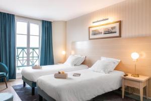 Un ou plusieurs lits dans un hébergement de l'établissement SOWELL HOTELS Le Beach