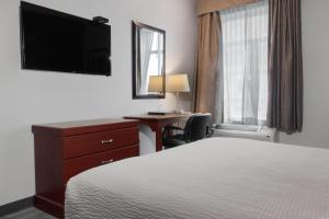 A television and/or entertainment center at Days Inn by Wyndham Hamilton - Downtown