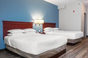 A bed or beds in a room at Days Inn by Wyndham Hamilton - Downtown