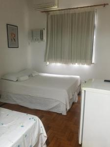 A bed or beds in a room at Hotel Fagundes Varela