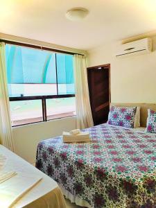 A bed or beds in a room at Pousada Delícias do Mar