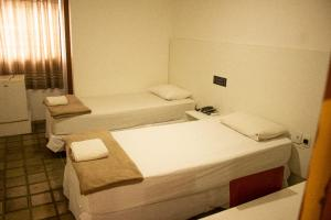 A bed or beds in a room at Caruaru Pallace Hotel