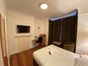 A bed or beds in a room at Buckingham Hotel