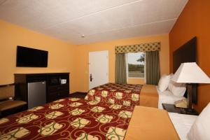 A bed or beds in a room at Budgetel Inn Glens Falls-Lake George