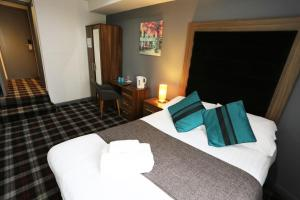 A bed or beds in a room at The Huddersfield Hotel
