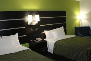 A bed or beds in a room at Quality Inn & Suites Bedford West