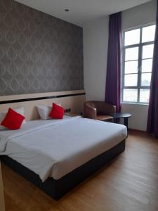 A bed or beds in a room at Blitz Hotel Batam Centre