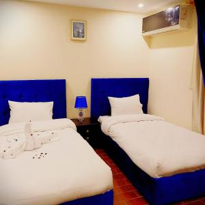 A bed or beds in a room at Golden Pyramids Inn