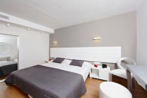 A bed or beds in a room at Hotel & Spa S'Entrador Playa