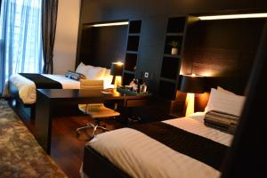 A bed or beds in a room at The One Boutique Hotel