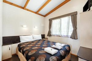 A bed or beds in a room at Golden Country Motel and Caravan Park