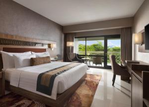 A bed or beds in a room at Royal Ambarrukmo Yogyakarta