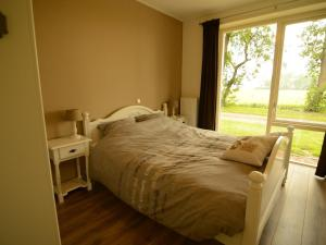 A bed or beds in a room at Boutique Holiday Home in Workum with Garden