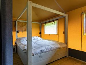 Een bed of bedden in een kamer bij Alluring Tent Lodge in Alphen with Hot Tub and Garden