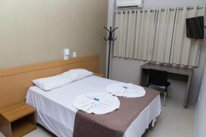 A bed or beds in a room at Hotel Astória Maringá