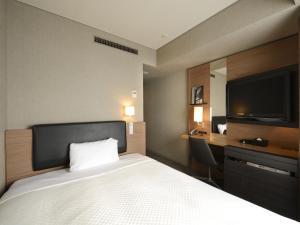 A bed or beds in a room at HOTEL UNIZO Osaka Yodoyabashi