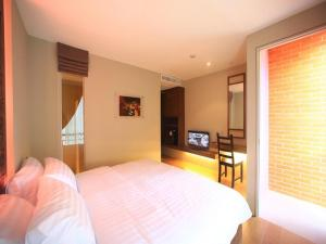 A bed or beds in a room at Silom One