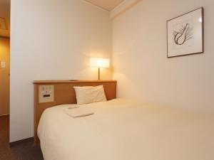 A bed or beds in a room at AkishimaStationHotel TOKYO