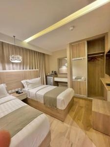 A bed or beds in a room at Twins Hotel