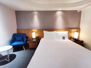 A bed or beds in a room at Azure Hotel