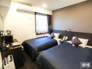 A bed or beds in a room at Hotel Livemax Yokohama Stadium Mae