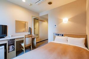 A bed or beds in a room at Kanazawa Central Hotel